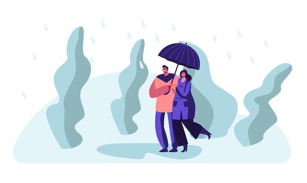 Glückliches liebespaar, das hände hält, die im park bei regnerischem wetter unter regenschirm gehen