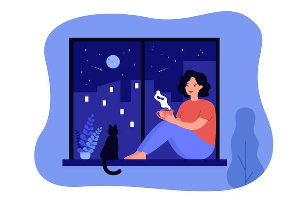 Glückliches mädchen, das am fenster nahe katze sitzt und heißes getränk trinkt. frau, die tee oder kaffee in der nacht genießt