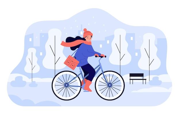 Glückliches mädchen, das fahrrad im winterpark reitet. junge weibliche karikaturradfahrerin auf fahrradradfahren entlang der straße der kalten verschneiten stadt
