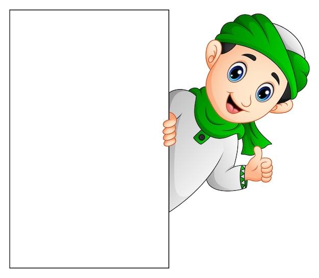 Glückliches moslemisches kind, das leeres zeichen hält und daumen aufgibt