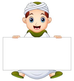 Glückliches moslemisches kind, das leeres zeichen hält