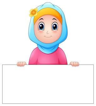 Glückliches moslemisches mädchen, das den blauen schleier leeres zeichen halten trägt
