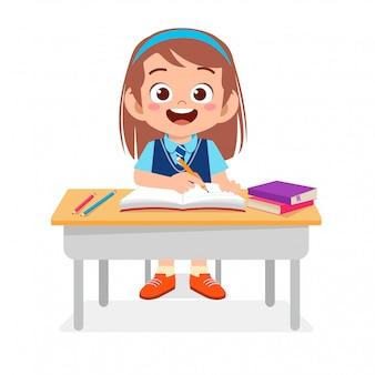 Glückliches nettes kind, das auf netter tabelle studiert