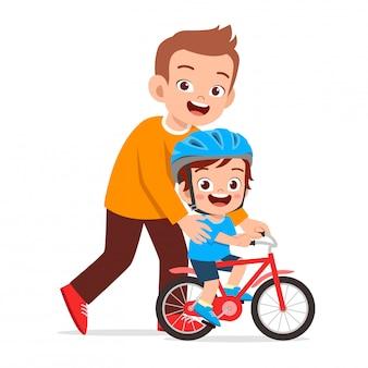 Glückliches nettes kinderjungen-reitfahrrad mit vati