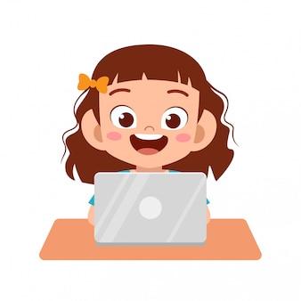 Glückliches nettes kindermädchen, das laptop verwendet, um hausarbeit zu tun