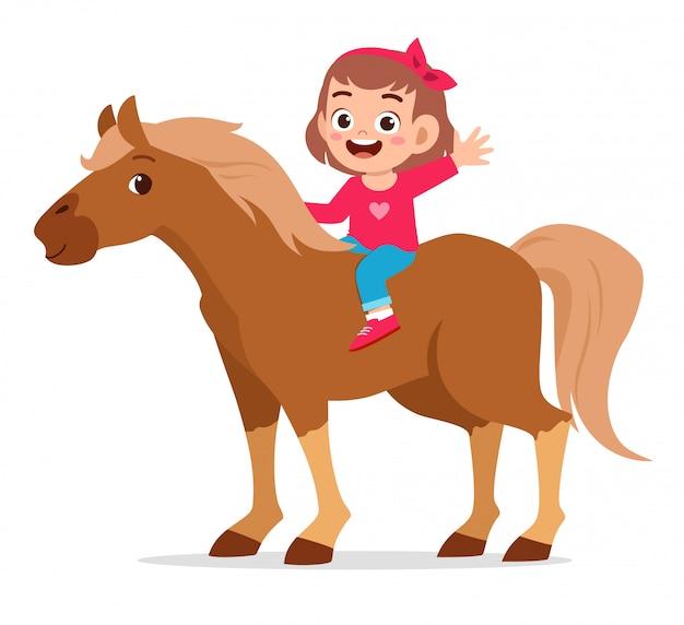 Glückliches nettes kindermädchen, das nettes pferd reitet