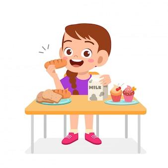 Glückliches nettes kindermädchen essen gesundes lebensmittel