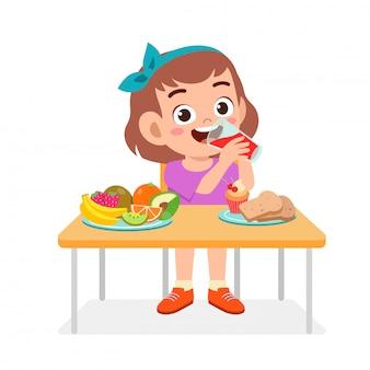 Glückliches nettes mädchen essen gesundes lebensmittel