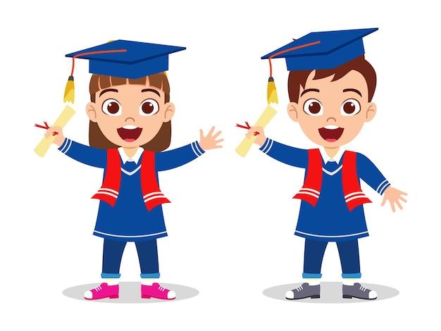 Glückliches niedliches kind graduiert jungen und mädchen, die mit zertifikat stehen und lokalisiert auf weißem hintergrund winken