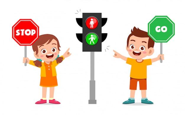 Glückliches niedliches kind jungen und mädchen mit verkehrszeichen