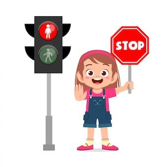 Glückliches niedliches kindermädchen mit verkehrszeichen