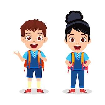 Glückliches niedliches kindjunge und -mädchen, die bereit stehen, zur schule zu gehen und mit fröhlichem ausdruck zu zeigen
