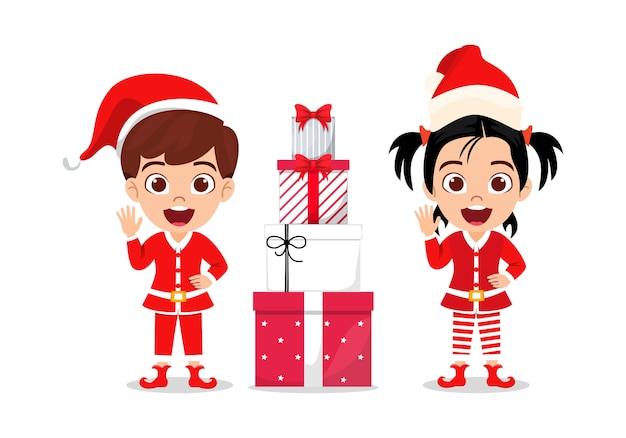 Glückliches niedliches kindjunge und -mädchen, die fröhliche charismas mit geschenkboxen winken und feiern, lokalisiert auf weißem hintergrund