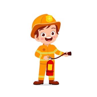 Glückliches niedliches kleines kind, das feuerwehruniform trägt und feuerlöscher hält