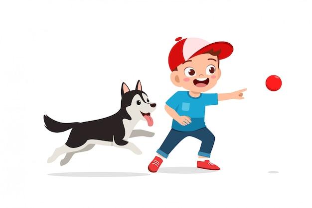 Glückliches niedliches kleines kind jungenmädchen spielen mit haustier hund