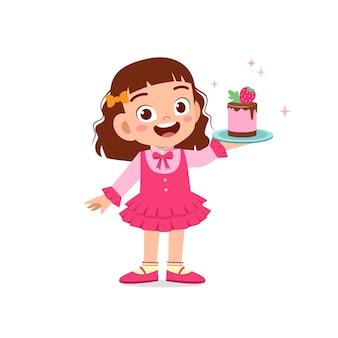 Glückliches niedliches kleines kindermädchen, das kellneruniform trägt und geburtstagstorte hält