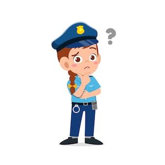 Glückliches niedliches kleines kindmädchen, das polizeiuniform trägt und mit fragezeichen denkt