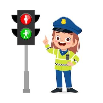 Glückliches niedliches kleines mädchen, das polizeiuniform trägt und neben ampel steht