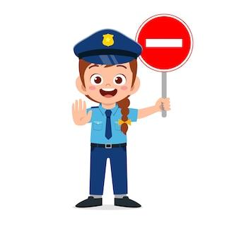 Glückliches niedliches kleines mädchen, das polizeiuniform trägt und stoppschild hält