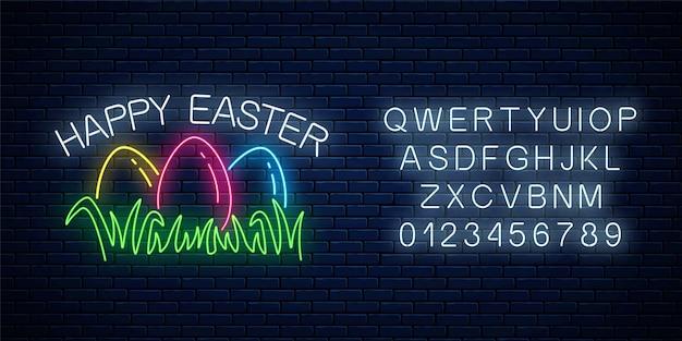 Glückliches ostern leuchtendes schild mit farbigen eiern auf gras mit alphabet im neonstil auf dunklem backsteinmauerhintergrund.