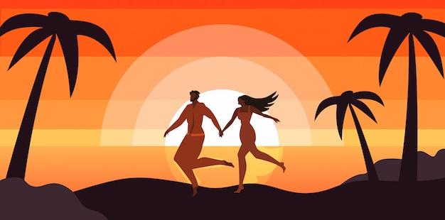 Glückliches paar, das am sonnenuntergang-tropischen strand sich entspannt.