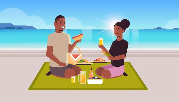 Glückliches paar, das auf decke sitzt, die hot dogs und mais-afroamerikaner-mannfrau isst, die zeit zusammen am strandpicknickkonzept-seestückhintergrund flach in voller länge horizontal verbringen