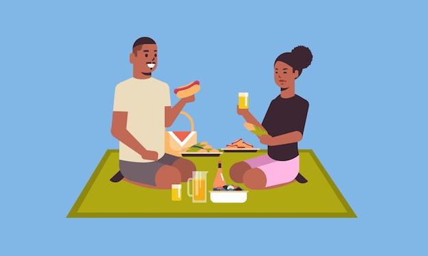 Glückliches paar, das auf decke sitzt und hot dogs und mais isst
