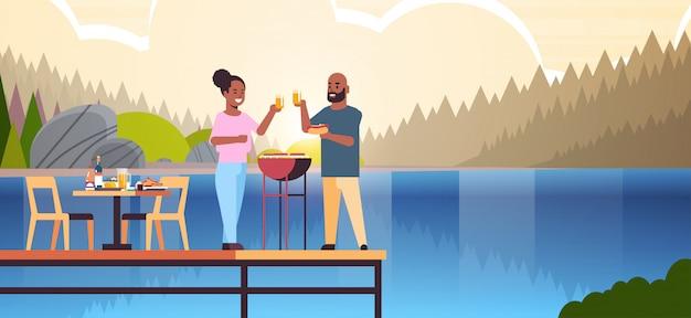 Glückliches paar, das hot dogs auf grill vorbereitet und saft afroamerikanermannfrau in der liebe steht, die auf hölzernem pier steht und picknickkonzept flussuferlandschaftshintergrund in voller länge horizontal hat