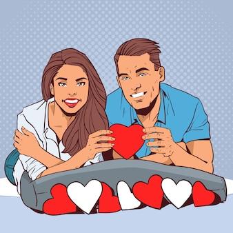 Glückliches paar, das rotes herz-lächelnden mann und verliebte frau über komischem pop-art style valentine day celebration concept hält