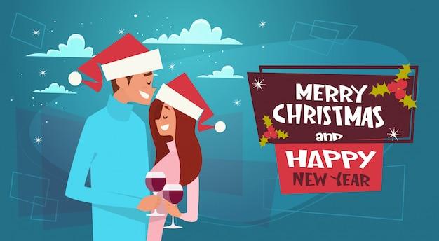 Glückliches paar in santa hats auf frohe weihnachten und happy new year poster umarmen