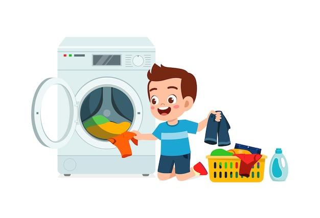 Glückliches süßes kind macht wäsche mit waschmaschine