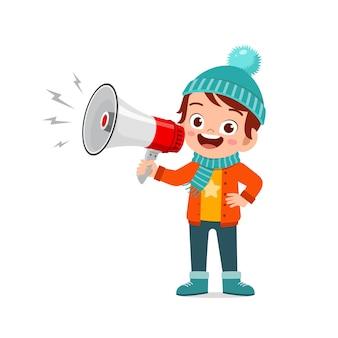 Glückliches süßes kleines kind, das megaphon in der wintersaison hält und warme kleidung trägt