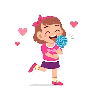 Glückliches süßes kleines kind mädchen essen süßigkeiten und süßigkeiten