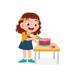 Glückliches süßes kleines kindermädchen, das eine geburtstagstorte kocht