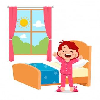 Glückliches süßes kleines mädchen wacht am morgen auf