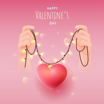 Glückliches valentinstag-konzept mit hand, die lichtgirlande und herzanhänger auf glänzendem rosa hintergrund hält.