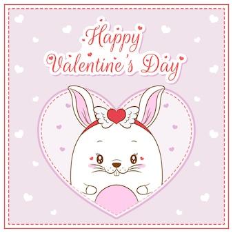 Glückliches valentinstag niedliches häschenmädchen, das postkarte großes herz zeichnet