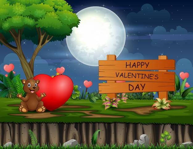 Glückliches valentinstagzeichen mit einem bären und rotem herzen in der nacht
