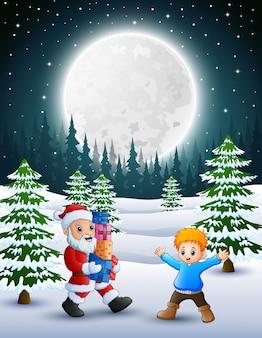 Glückliches weihnachten mit weihnachtsmann, der ein kastengeschenk und einen kleinen jungen im winter hält
