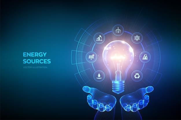 Glühende glühbirne mit energieressourcenikonen in den händen. strom- und energiesparkonzept. energiequellen.