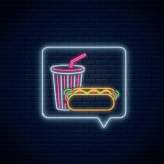 Glühendes neonzeichen von hot dog und sodagetränkbecher im nachrichtenbenachrichtigungsrahmen auf dunklem backsteinmauerhintergrund. symbol für essen und trinken in der sprechblase im neonstil. vektor-illustration.