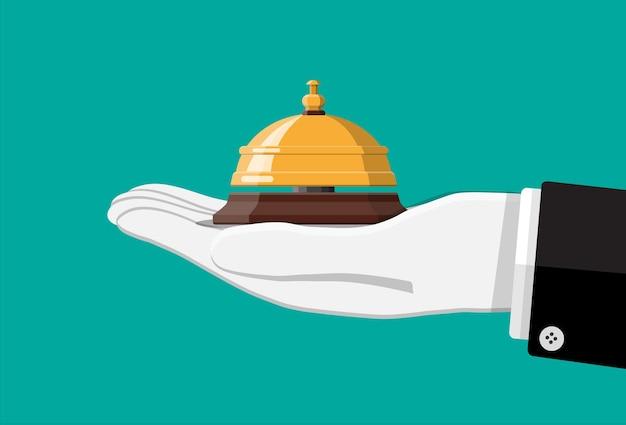 Goldene serviceglocke in der hand.