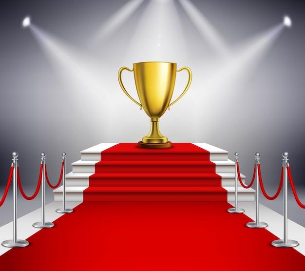 Goldene trophäe auf der weißen treppe bedeckt mit rotem teppich und durch scheinwerfer belichtet