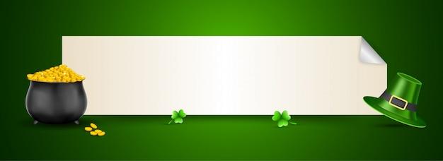Goldener münztopf oder kessel mit koboldhut, kleeblattblättern und weißem lockenpapier gegeben für nachricht auf grün