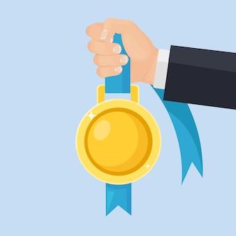 Goldmedaille mit blauem band für den ersten platz in der hand. trophäe, gewinnerpreis im hintergrund. goldenes abzeichen-symbol. sport, geschäftserfolg, sieg.