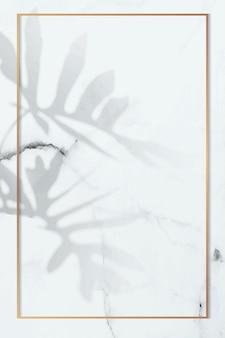 Goldrahmen mit philodendron-radiatum-blattmuster auf weißem marmorhintergrund