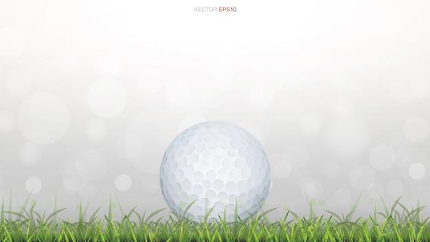 Golfball auf grünem grasfeld mit hellem unscharfem bokehhintergrund