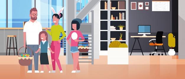 Große familie auf glücklichen ostern-eltern und den kindern, die frühlingsurlaub feiern, tragen bunny ears und halten körbe über wohnzimmer-innenraum