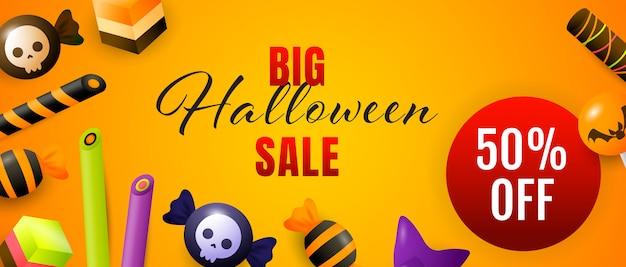 Große halloween-verkaufsbeschriftung mit süßigkeiten und bonbons