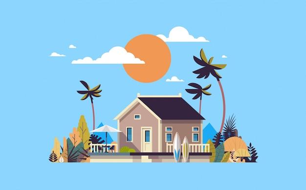 Große sommervilla haus regenschirm surfbrett sonnenuntergang palmen